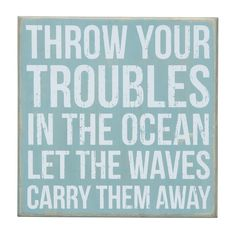 "In the Ocean Sign. Weathered and rubbed wood creates wall art that looks aged from wind, sand and sun. ""Throw your troubles in the ocean let the waves carry them away"" in white creates a relaxing color palette atop the sky blue. Designed in a box style to allow for either hanging on the wall or sitting atop a table."