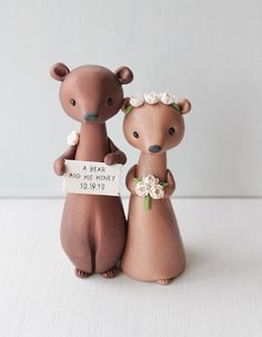 Brown bear wedding cake topper for woodland wedding theme, the groom is holding a sign A bear and his honey, the bride is adorned with ivory peonies. This animal wedding figurine is sculpted in polymer clay with mica mineral powder added for subtle pearly shine and elegant marble