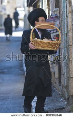 JERUSALEM - MARS 09 : Ultra Orthodox man holding Mishloach Manot during Purim in Mea Shearim Jerusalem on Mars 09 2012 , Mishloach Manot is traditional food gifts given during Purim - stock photo