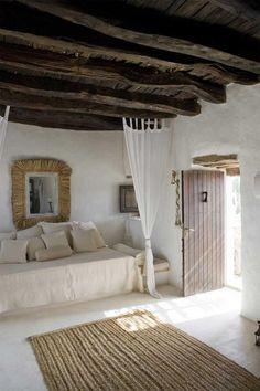 Minimalist, rustic, neutral tone bedroom. Dark wood ceiling is a beautiful focal point.