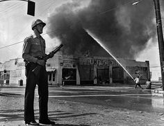 August A Los Angeles County Sheriff's deputy armed with a Hi-Standard riot shotgun stands guard while fire fighters attempt to put out a structure fire during the Watts riots. Watts Riots, Los Angeles Police Department, 50 Years Ago, Remember The Time, Mountain Man, New Chapter, Law Enforcement, America, Deputy Sheriff