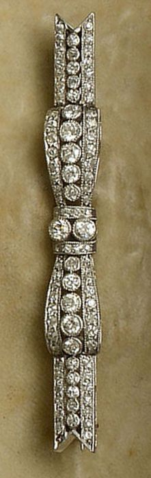 An Edwardian diamond ribbon bow brooch.  The slim bow design set throughout with brilliants and single-cut diamonds, millegrain edged, white precious metal mounted, unmarked, with case, length 5.2cm.