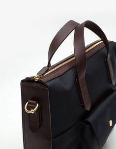 Waterproof canvas and leather briefcase from Mismo. Features inside laptop compartment, removable leather strap, leather carry handles, snap button outside pocket, and zip closure.   100% Cotton Canvas and 100% Leather