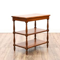 This country chic tiered side table is featured in a solid wood with a rustic cherry finish. This end table has 3 shelf tiers and carved spindle leg rails. Perfect for displaying books or storing linens! #americantraditional #tables #endtable #sandiegovintage #vintagefurniture
