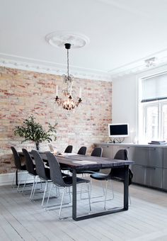 """Authentic New Yorker look with exposed bricks and a massive wooden table - in the middle of the table there is an element to create """"open fire""""."""