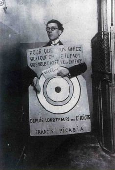 André Breton at a Dadaist festival in Paris (March 27, 1920), wearing a sandwich board with text from Francis Picabia:  ...