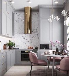Modern light grey kitchen with rose accents and brass hood