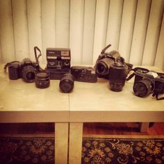 004/365 Jan 4 My toy collection over the years.   From L-R;  Minolta Maxxum 3xi, Polaroid 600 One Step Flash, Kodak KB10 35mm point and shoot, Nikon D3000 w/ battery grip, Asahi Pentax K1000.  Lenses from L-R; Minolta AF 50mm, Sigma 35-70mm, and Nikon 55-200mm.