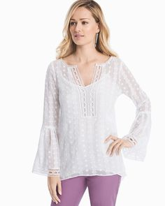 """It's not summer without a white blouse, and ours is as gorgeous as it can get thanks to the tonal embroidery, ladder trim detail and bell sleeves. It's a go-to on weekends and instantly adds a dose of charm to denim.  White tonal embroidered blouse Attached white cami lining Bell sleeves Ladder trim and pom-pom detail along neckline and sleeves Regular: Approx. 27"""" from shoulder Petite: Approx. 25 5/8"""" from shoulder Polyester. Machine wash cold. Imported Model is 5'9 1/2"""" and wearing XS or…"""