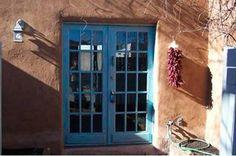 Blue door and chile ristra says Mi Casa es tu Casa - Welcome