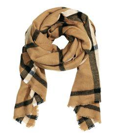 En scarf i vävd kvalitet med fransiga sidor. Storlek 105x180 cm.