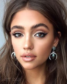Contour. Shimmery light shadow on lids & inner corners. Brown matte shadow in creases, lower lash lines & outer corners. Rim eyes w/ black. Black winged liquid liner. Mascara. Nude lipstick & lipgloss.