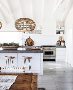 White kitchen cupboards, dark stone countertops, white walls and accented with rattan pendants and baskets all make this a perfect kitchen. #beachhousedecorrustic