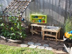 Outdoor kitchen for making mud pies! Recycled shelves, upcycled sink for making mud. www.overlookpreschool.com