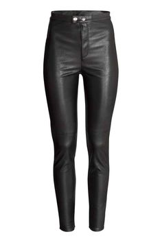 Calças em pele sintética: Calças em pele sintética stretch. Têm cintura alta, pernas estreitas com costuras nos joelhos e braguilha com fecho éclair e botões de pressão.