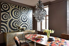 A turn-of-the-century French chandelier punctuates a Moscow kitchen accented with decorative Balinese wall panels and a floral-printed vintage table.Moscow kitchen