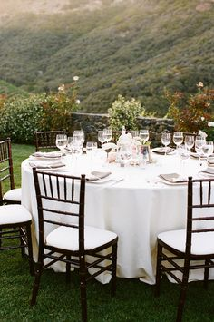 Round tables with white tablecloths & dark chiavari chairs