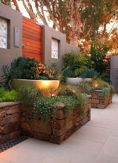 Raised stone planters, up lighting. Nice colors in plants. For up against house? Find your dream #StonePlanters for your garden at www.exceptionalstone.com/product-category/patio-and-landscaping/stone-garden-planters/ #Moderngarden