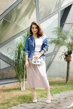 Look da Bruna Unzueta durante SPFW. Produção mais Hi-Lo combinando uma saia midi metalizada com t-shirt e jaqueta jeans.