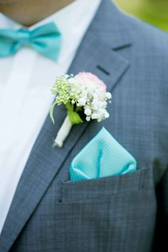 romantischer Anstecker Bräutigam mit türkiser Fliege und Einstecktuch an einem grauen Anzug.