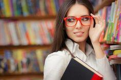 Mujer inteligente colocándose sus gafas rojas con una mano y sujetando libros con la otra