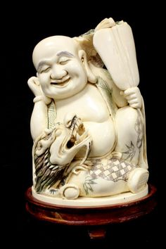 Chinese hand carved polychromed ivory figure depicting a happy seated Buddha with dragon. In his left hand is a paddle fan and the dragon is holding dragon jewel in right claw.