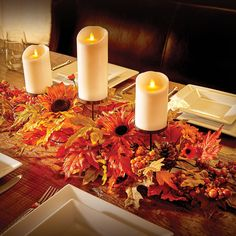 Decorate your Thanksgiving table with a fall centerpiece that's covered in bright colored leaves, large sunflowers and realistic-looking berries.