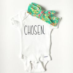 Chosen Onesie  Adoption is a beautiful thing! Announce your adoption with this precious onesie. Available sizes include newborn, 3 mos., 6 mos., 9 mos., and 12 months.  Onesie is available with or without the top-knot headband. Made with heat transfer material for a vibrant and sharp design. Machine wash inside out on gentle cycle and lay flat to dry. Shipping: Turnaround time is 3-5 days plus 3-5 days for first class mail. Priority mail and rush orders available for an additional fee. All…
