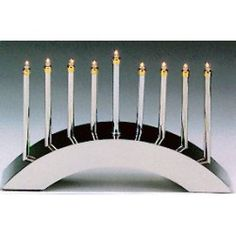 """Electric menorah. This arched menorah is a stand out with its sleek and contemporary design. No need to deal with melted candle wax with this high polished silver-plated menorah. The low voltage menorah measures 10 x 6.5"""""""