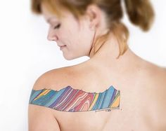 Geologist Helen Malendas showing her geological cross section tattoo.