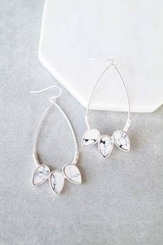 """Brushed metal teardrop hoops with marble stone accents. Details: - 2 3/4"""" drop - Plated"""