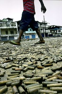 War Underfoot -2003  Picture of bullet casings carpet a street in Monrovia (the capital of Liberia), at the heart of the battlefield between government and rebel soldiers. Businesses closed for weeks as the battle raged. Carolyn won pulitzer prize in 2004 with the set of pictures containing this one.
