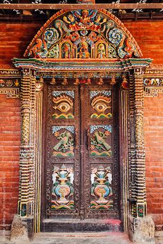 Intricately carved wooden doors in a temple in Kathmandu, Nepal.