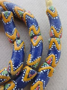 A beautiful strand of 27 Krobo glass beads from Ghana, on raffia 30 inches long. Each handmade bead measures approximately 10mm x 25mm. The hole is 4mm.