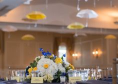 Unique wedding theme- rain or shine, yellow, white and blue flower centrepiece, umbrellas hanging from ceiling, navy blue linens. River House in downtown St. Augustine.