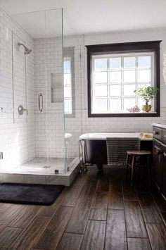 wood tile floor, white subway tile with dark grout, black window trim - basement bath