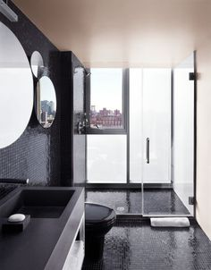 Loving the edgy black ebony look of this floor to ceiling shower with glass on two sides in this urban loft bathroom.