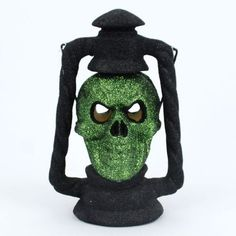 """SKULL HEAD LANTERN Halloween GOTHIC DEAD FUN Lights Up changes Colors by 180. $16.99. Light up the night with this totally creepy Skull Head lantern! About 12"""" tall, evil looking skull is covered in a dead green glitter shade and he lights up (light inside changes colors and flickers), with 2 """"AA"""" Batteries (not included). Put this guy on a table and light him up for some eerie creepy atmosphere. NEW. Save 32%!"""