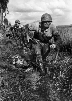 American Marines race past a dead enemy soldier. Korea, September 1950.