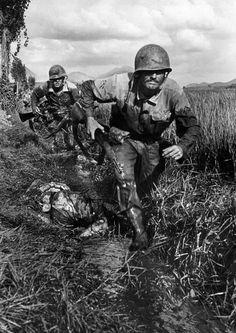 American Marines race past a dead enemy soldier. Korea, September 1950.