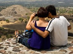 Young couple looking at ruins through binoculars