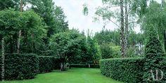 Живые изгороди и конусы в этой части сада созданы из боярышника овальнолистного. В центре лужайки — ирга круглолистная.