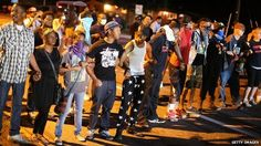 Demonstrators in Ferguson, Missouri, link arms to protest the shooting of Michael Brown - 13 August 2014