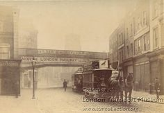 Double deck horse-drawn knifeboard tram no 296, operating between Aldersgate Street and Clapton. Vehicle is seen in service, and has just passed under the North London Railway bridge across Mare Street at Hackney. The tram is empty, as is the road, apart from another tram just visible behind the first (circa 1888).