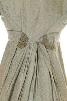 An ice-blue figured silk pelisse robe, circa 1820. the bodice with hussar-style frogging, trimmed with fringed passementerie and silk covered buttons, the puffed mancherons and cuffs en tablier with satin piping and buttons, the hem with deep border of blue plush and flecked fringing which gives the effect of feathers,