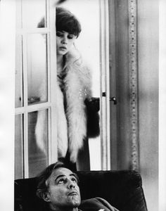 """Maria Scheider's hair in """"Last Tango in Paris"""": heavy bangs, a low chignon, wavy tendrils. She wore a hat with this hairstyle."""