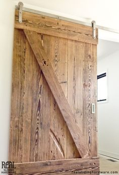 Deep knots and grooves add rustic character to this sliding barn door that divides a stairwell from the upstairs loft.