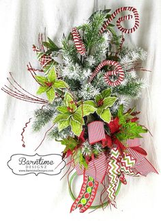 Christmas wall or door swag made on a vintage iron scroll. Colorful & cheery for your decor! Info@barntimedesignz.com #barntimedesignz #christmas #swag #wreath #holidayswag #poinsettias #doordecor