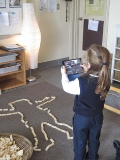 """""""I am taking a photo to remember."""" A child captures her creation, so that she may count the number of blocks used to measure her friend."""