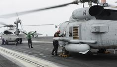 """GULF OF OMAN (July 15, 2013) - Aviation Structural Mechanic Airman Aubrey Hill, a native of Midland, Calif., assigned to the """"Wolf Pack"""" of Helicopter Maritime Strike Squadron (HSM) 75, waves down the pilots in preparation for a fuel load on an MH-60R Seahawk helicopter on the flight deck of the aircraft carrier USS Nimitz (CVN 68)."""